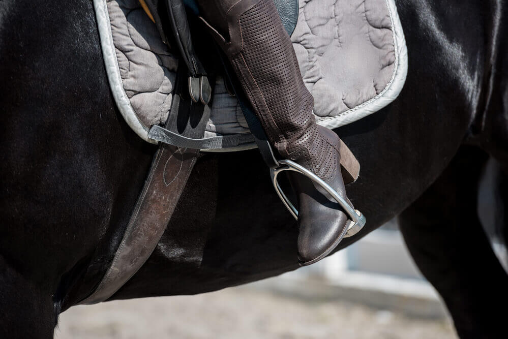 the view of a boot of a person riding a horse