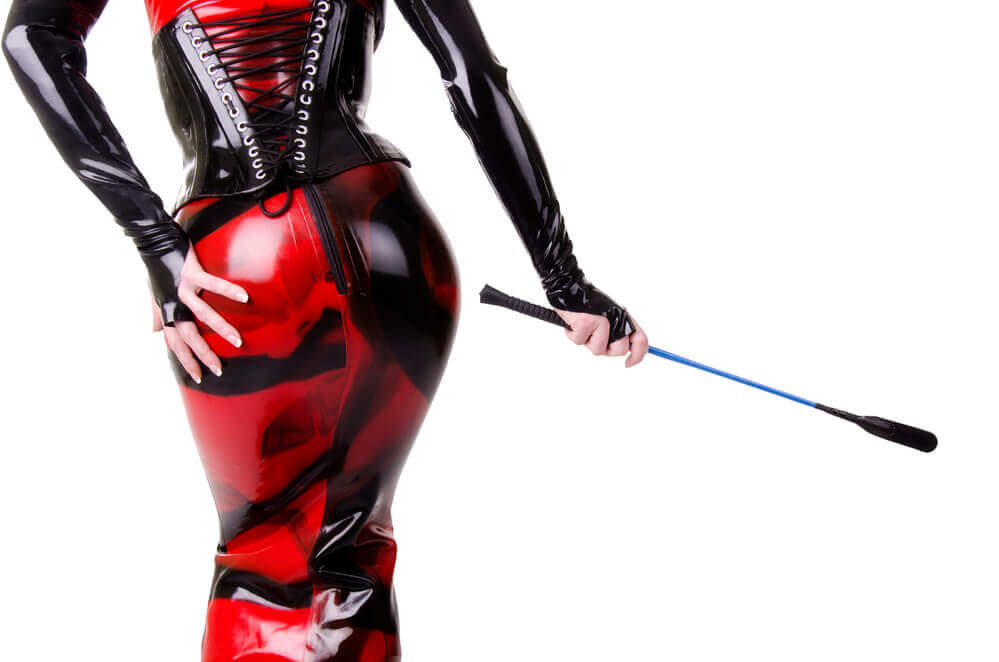 feminine person dressed in red and black leather and latex holding a riding crop